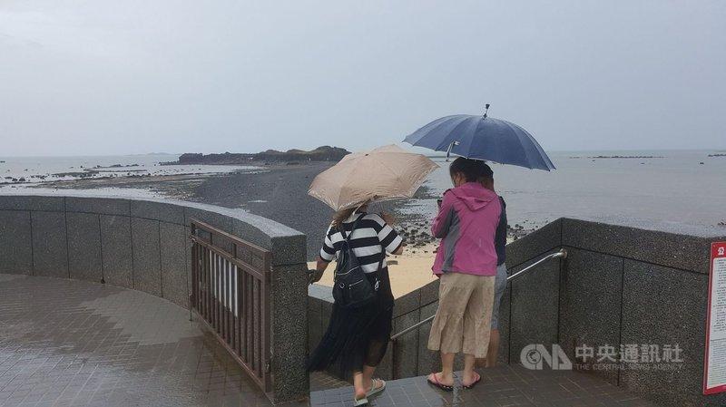 國內COVID-19疫情警戒降至2級,澎湖縣政府指出,澎湖各觀光景點大都採總量管制,最熱門的澎湖北寮摩西分海步道受到雨勢影響,31日上午退潮時,只見有少部分的遊客在雨中持傘下海體驗。中央社  110年7月31日