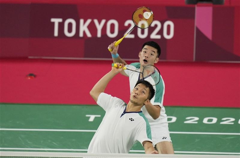 東京奧運羽球男雙31日金牌戰,台灣組合王齊麟(後)與李洋(前)拿下首局。(美聯社)