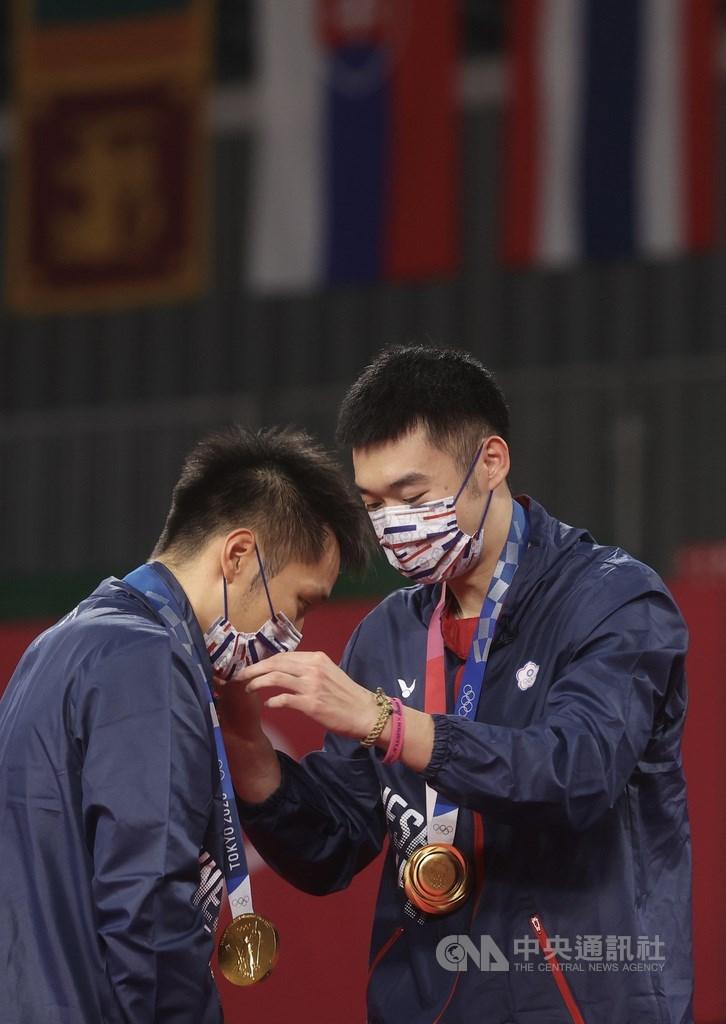 東京奧運羽球男子雙打傳捷報,台灣好手李洋(左)、王齊麟(右)31日成功為台灣拿下奧運羽球史上首金,兩人在頒獎台上為彼此掛上這面合力奮戰到手的獎牌。中央社記者吳家昇攝 110年7月31日