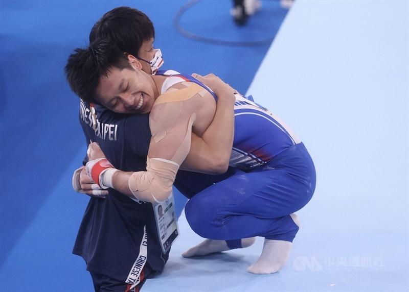 東京奧運體操男子鞍馬單項決賽1日晚間登場,台灣好手李智凱(右)成功展現拿手「湯瑪士迴旋」,精彩完成一連串動作,並一掃陰影完美落地,他在下馬後開心與場邊教練相擁。中央社記者吳家昇攝 110年8月1日