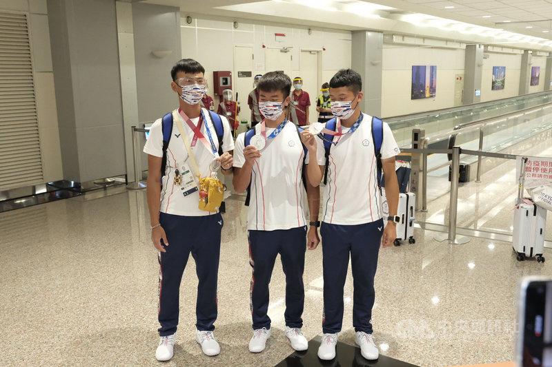 拿下本屆東京奧運射箭男子團體銀牌的台灣好手魏均珩(左)、湯智鈞(右)、鄧宇成(中)1日下午結束賽程,搭機返抵國門,也開心秀出合力奮戰奪得的銀牌。中央社記者吳睿騏攝  110年8月1日