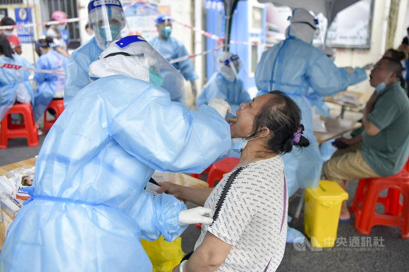 中國COVID-19疫情延燒,從7月20日南京機場開始傳播,湖南張家界又成為另一個散發源頭,海南島8月1日也出現1例確診者。工作人員1日對確診病例曾去過的海口頭舖農貿市場相關人員進行核酸採樣。(中新社提供)中央社  110年8月1日