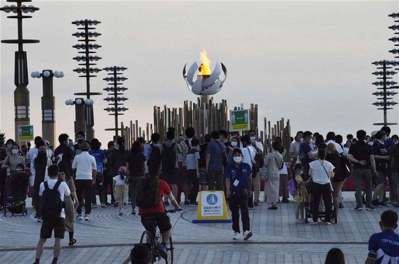 奧運主辦地日本東京COVID-19疫情持續升溫,2日新增病例創週一新高紀錄。圖為7月25日東京都台場「夢之大橋」上的奧運聖火台湧入人潮。(共同社)