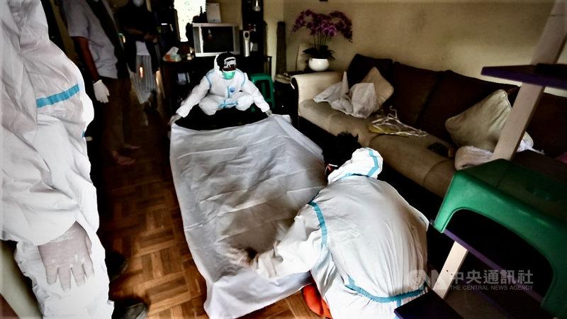 依伊斯蘭教義,人死後的軀體僅以白棉布包覆,不用棺木直接土葬。印尼志工協助家屬以符合防疫的方式安葬染疫死者。圖為志工在死者家裡準備白棉布,攝於7月30日。中央社記者石秀娟茂物攝 110年8月2日