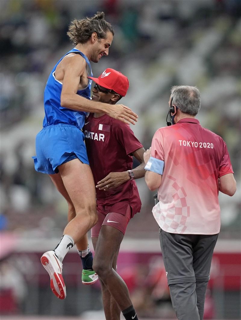 義大利選手坦貝里(左)1日與卡達跳高王子巴爾希姆(中)在東京奧運男子跳高項目雙雙以2米37成績拿下金牌,讓奧運田徑賽事繼1912年以來再次出現雙金牌得主。坦貝里與巴爾希姆得知比賽結果高興地擁抱對方。(美聯社)