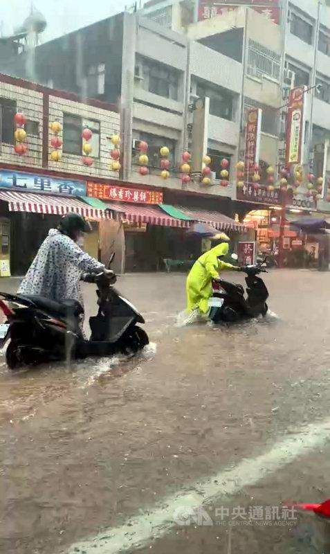 嘉義縣市2日上午降豪雨,新港奉天宮前嚴重積水,機車騎士需下車才能通行。(新港奉天宮提供)中央社記者黃國芳傳真 110年8月2日