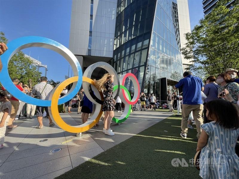 本屆奧運主辦城市東京與其他地區的COVID-19確診激增,日本官員表示,為免醫療體系吃緊,抗疫策略將改為著重收治重症、或有可能變成重症的患者住院。圖為7月23日東京奧運主場館國立競技場晚間舉行開幕式,許多民眾到場館周邊拍照。(中央社檔案照片)