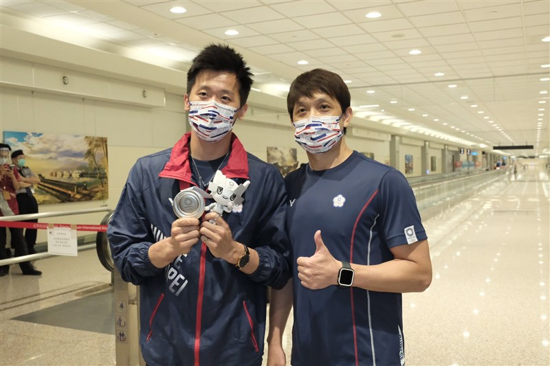 拿下東京奧運男子鞍馬單項決賽銀牌的體操選手李智凱(左)3日與教練林育信(右)返台,李智凱下機秀出台灣體操史上首面奧運獎牌。中央社記者吳睿騏攝 110年8月3日