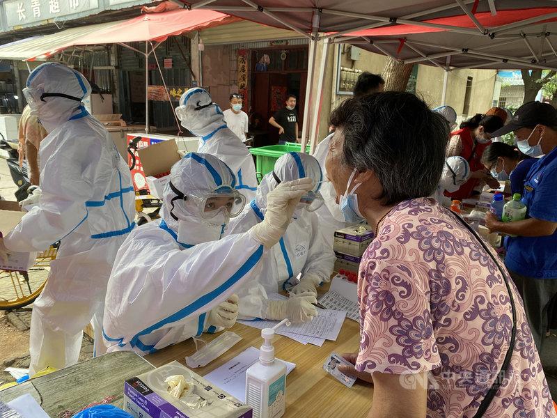 中國湖北省武漢市近日再現COVID-19本土疫情,迄今累計確診12例。官方4日指出,目前已完成的2例樣本測序結果顯示為Delta變異病毒株。圖為3日,醫護人員為武漢經開區居民進行核酸採樣。(中新社提供)中央社 110年8月4日