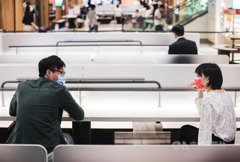 國內COVID-19疫情趨緩,台北市、新北市3日起有條件開放餐飲內用,台北101購物中心美食街座位區架設防疫透明隔板,民眾也保持安全社交距離進行交談。中央社記者鄭清元攝 110年8月3日