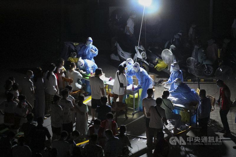 才遭暴雨肆虐的河南鄭州,近日又爆發COVID-19本土疫情,截至4日晚上6時,第一輪普篩已檢出101個病例。圖為1日凌晨,鄭州醫護人員漏夜對爆發疫情的二七區居民進行核酸檢測。(中新社提供)中央社  110年8月4日