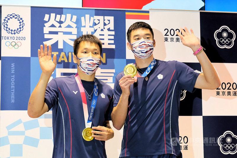 台灣羽球男雙搭檔「麟洋配」王齊麟(右)、李洋(左)勇奪本屆東京奧運羽球男雙金牌,為奧運羽球台灣史上首金,兩人4日搭機返台,開心揮手致意。中央社記者吳睿騏桃園機場攝 110年8月4日
