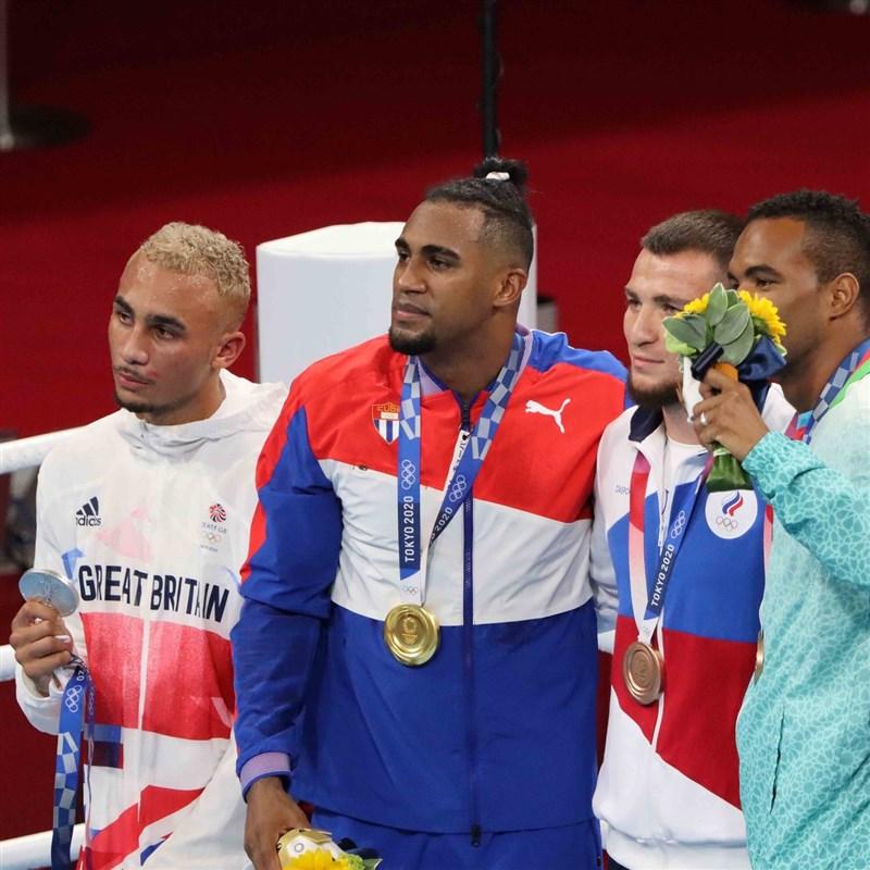 英國拳擊手惠塔克(左1)4日在東京奧運男子輕重量級決賽摘下銀牌,但他卻因對自己成績太失望,而在頒獎時不戴上獎牌,形成選手在比賽後抗議自己的罕見場面。(圖取自twitter.com/gbboxing)