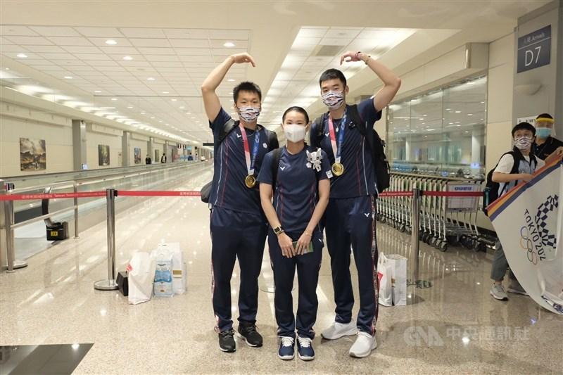 參加東京奧運的台灣羽球代表隊的教練及選手們4日返台,受到熱烈歡迎。其中拿下羽球男子雙打金牌的王齊麟(右)、李洋(左),與羽球女子單打銀牌戴資穎(中),更是大家矚目的焦點。中央社記者吳睿騏桃園機場攝 110年8月4日