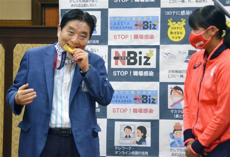 日本名古屋市長河村隆之(左)4日接見獲東奧女壘金牌的20歲投手後藤希友(右)時,竟拉下口罩大口咬奧運金牌,引發網友批評太失禮。(共同社)
