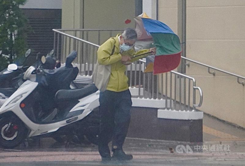中央氣象局表示,5日受颱風外圍環流影響,中南部地區有陣雨或雷雨,並有局部大雨或豪雨發生的機率。高雄有民眾在強風陣雨中行走時,傘差點開花。中央社記者董俊志攝 110年8月5日