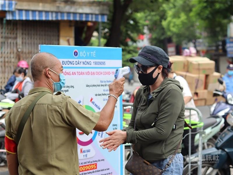 越南面臨迄今最大一波疫情,全國累計已17萬7800例確診、2327例死亡,其中多數是過去一個月出現在胡志明市。圖為7月28日越南有人員在傳統市場入口為民眾量體溫。(中央社檔案照片)