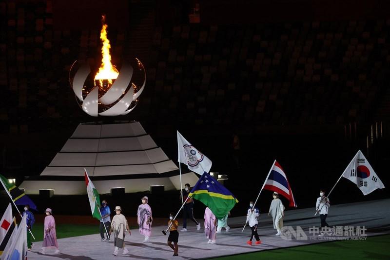 因疫情延期一年的2020東京奧運在結束連日來的激烈賽事競爭後,8日晚間舉行閉幕式,各國運動員代表高舉旗幟進場,開心參與本屆奧運最後一場盛大典禮。中央社記者吳家昇攝 110年8月8日