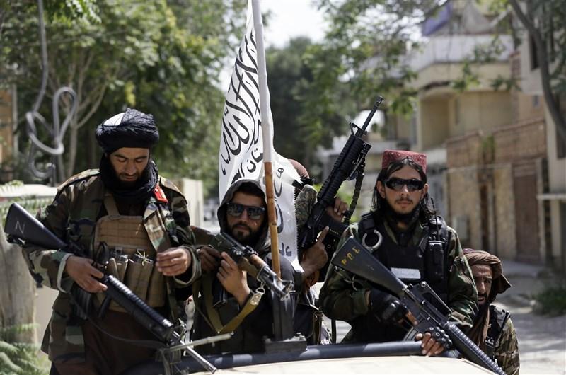 塔利班15日進入阿富汗首都喀布爾,逼迫政府和平轉移政權。圖為塔利班在喀布爾巡邏時展示旗幟。(美聯社)