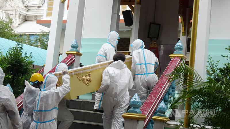 泰國第三波疫情嚴峻,8月中旬以來死亡人數每日新增破200人,寺廟協助火化死者屍體,圖為工作人員和僧侶穿上防護衣搬運棺材到火化爐前。中央社記者呂欣憓曼谷攝 110年8月31日
