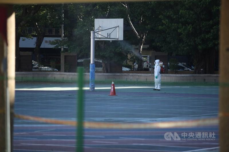 指揮官陳時中13日表示,松山某國中學生的奶奶確定染疫,研判為家戶群聚感染。圖為台北市環保局10日派人至學校籃球場消毒。(中央社檔案照片)