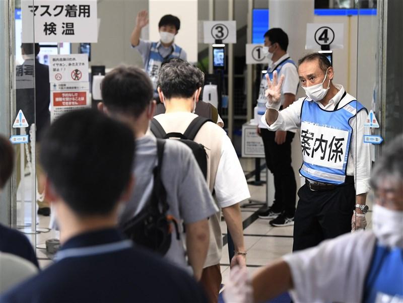 日本境內COVID-19疫情漸趨緩,專家指出疫苗接種是原因之一。圖為青少年在大阪大規模接種中心等待施打疫苗。(共同社)