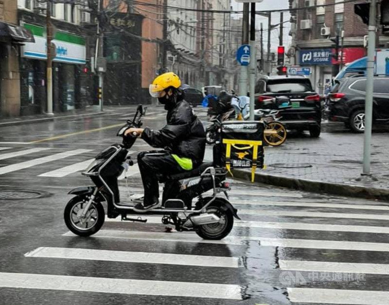 颱風璨樹(中國大陸稱燦都)為上海帶來風雨,不少人選擇叫外送解決吃的問題。雖然路上外送員明顯減少,但仍有人把握賺錢機會。圖為冒著風雨送餐的美團外送員。中央社記者吳柏緯上海攝  110年9月13日