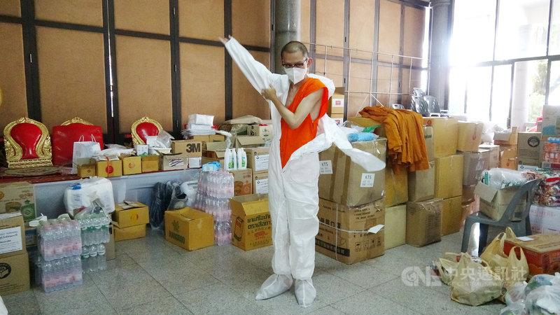 曼谷蘇堤瓦拉蘭寺副住持彭蓬穿上防護衣,準備前往附近社區協助民眾進行快篩和送藥品給確診民眾,這樣的任務從7月21日起沒有間斷。中央社記者呂欣憓曼谷攝 110年9月15日