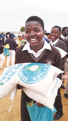 女學生雙手捧起重達20公斤的大米,很吃 力卻很開心。