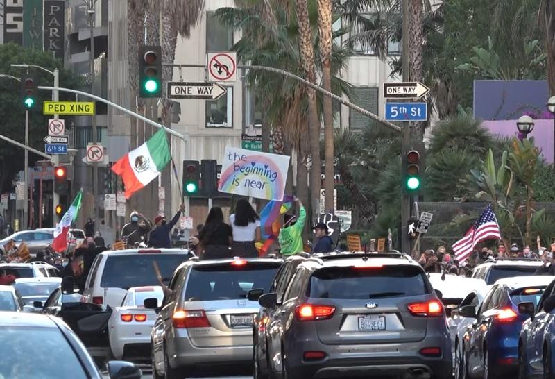 洛杉磯市中心慶祝拜登當選的人群車隊裡,除了美國星條旗,還可看到有人拿著墨西哥國旗與彩虹旗。(中央社林宏翰)