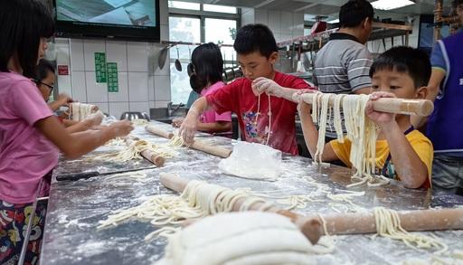 小學生將麵團切製成寬度3mm的手作烏龍麵。