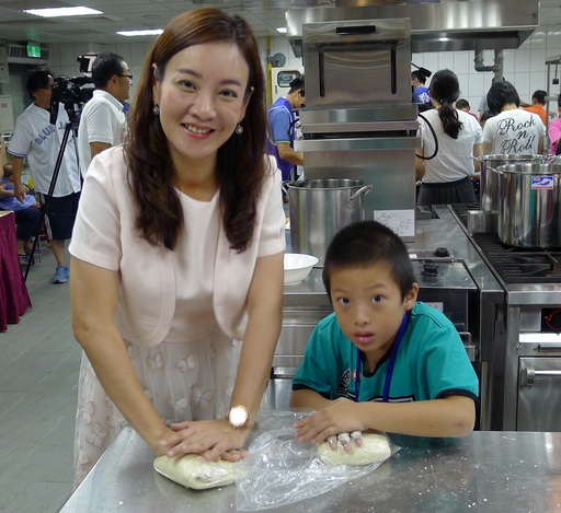 桃園市客家局長蔣絜安(左)與小學生一起同樂,將麵粉揉製成彈性極佳的麵糰。