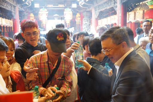 臺鹽董事長陳啓昱(右)發送「台鹽海洋鹼性離子水」給信眾,吸引人潮索取。