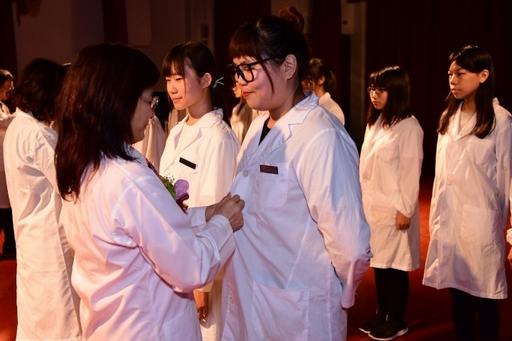 中華醫大醫技系舉行實習生授袍典禮,師長和業界學長返校為學弟妹扣實習白袍鈕扣及別名牌