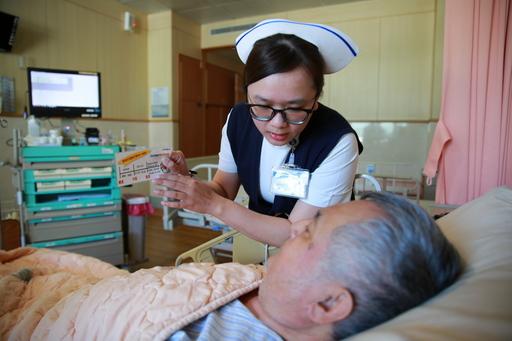 副護理長歐軒如以「創新CRBD評估量表」向郭先生詢問術後導尿管狀況。