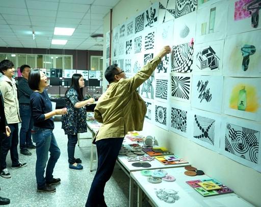 商設系徐宏文等位老師進行評審時(右一),為優秀作品貼上紅標。