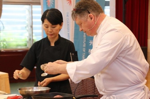 圖為米其林主廚Loïc Le Bail(右一)與臺灣觀光學院學生李碧艷(左一)在記者會上的料理示範