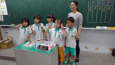員林國小學童拿著自己組的竹槍與大葉大學企管系大三生莊怡瑄(後排)開心合影