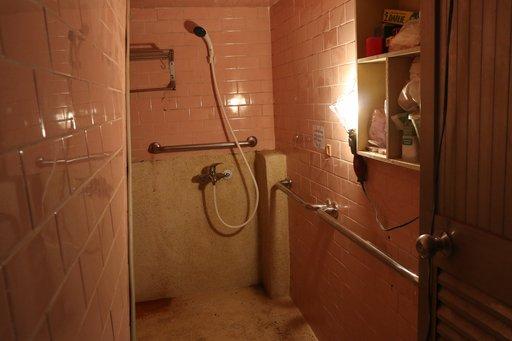 莊家修繕後的浴室,地面改為防滑抿石子地、更換淋浴龍頭,壁面新增扶手