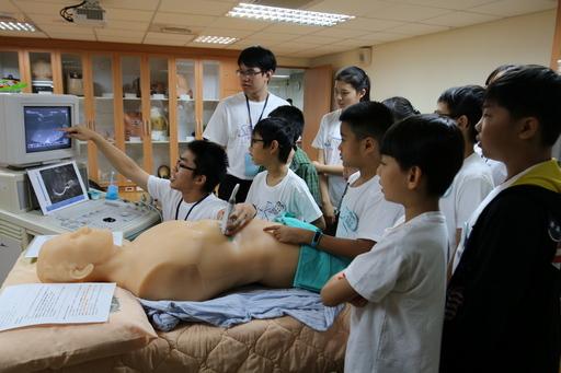 慈濟大學見晴服務隊的關主手把手帶著孩子操作超音波設備,小醫王們聽的入神,專注地從超音波影像中尋找肝臟的位置
