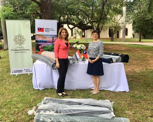 駐巴拉圭周麟大使夫人李潔女士(左)代表幫幫忙基金會捐贈愛心布料乙批,由巴國第一夫人辦公室計畫協調人Sully Cabrera(右)接受