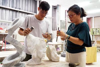 大葉大學造藝系廖秀玲主任(右)指導李伯元(左)創作石雕