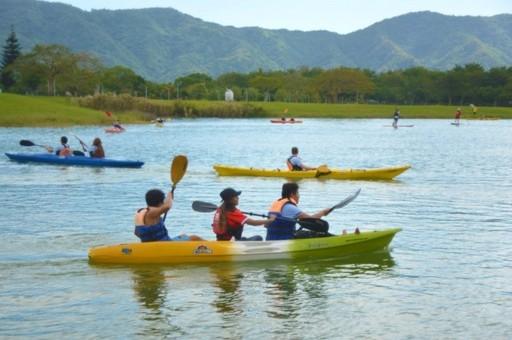 來賓及國際生駕駛獨木舟徜徉在東湖,映襯藍天白雲及綠野青山