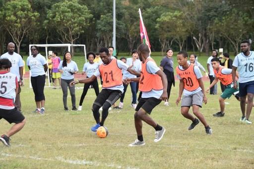 足球隊員緊盯著前方的球,場邊啦啦隊同樣緊張萬分