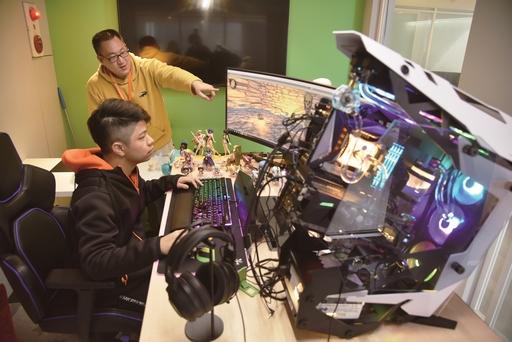 華梵大學攝影與VR設計學系學生在個人獨立空間設計電競遊戲,老師在旁指導。