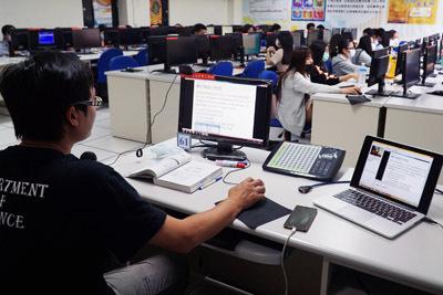 大葉大學財金系張椿柏老師(左)另外準備一台筆電,確認線上教學系統是否同步