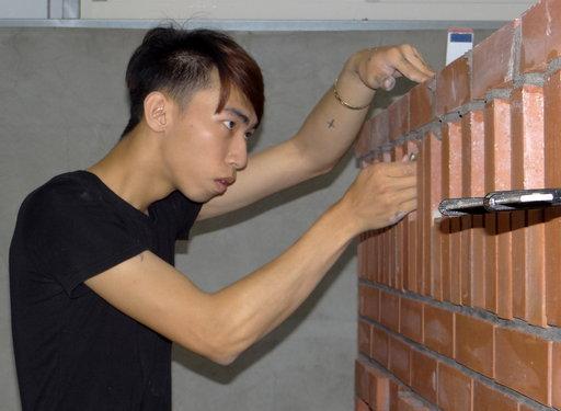 張育銘專注砌磚神情。