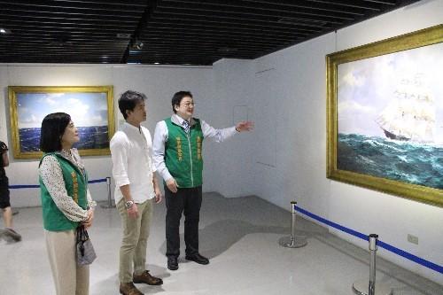 長榮海事博物館陳鈺祥館長(右)向謝哲青老師解說海洋畫作的故事。