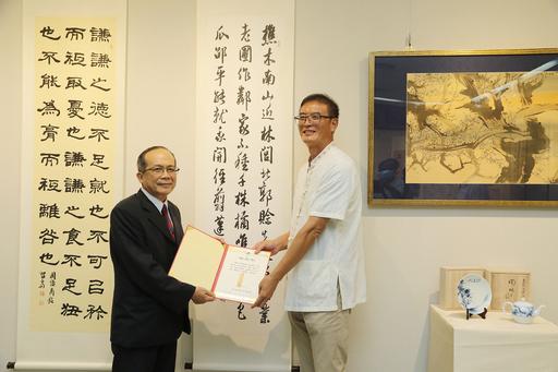 黃緯中(右)老師致贈書法作品一幅予中興大學藝術中心,由興大黃振文副校長頒贈感謝狀。