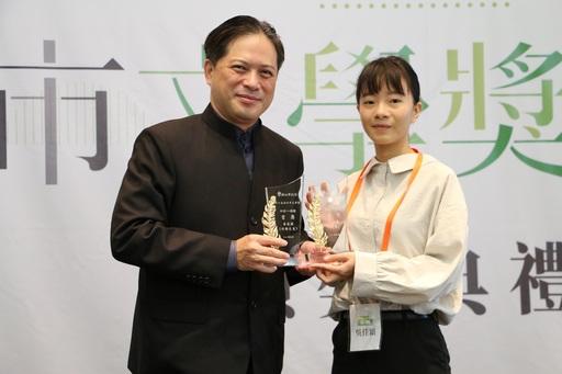 新北市副市長吳明機(左)親自頒發新詩及散文獎項給雙料得主吳佳穎(右)